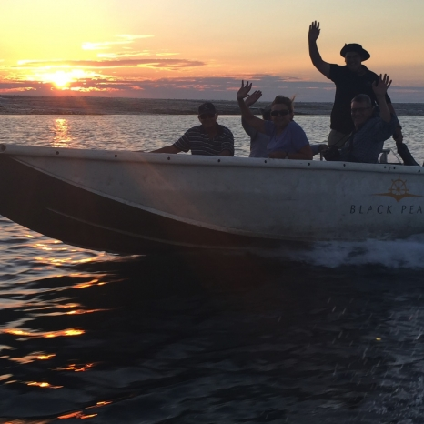 people waving on dinghy with sunset background
