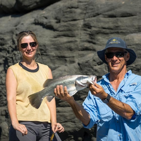 couple holding freshly caught barramundi