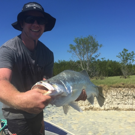 man with barramundi on beach