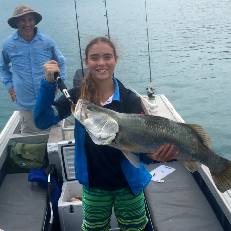 young girl holding caught barramundi fish
