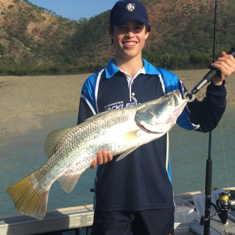 boy holding caught barramundi