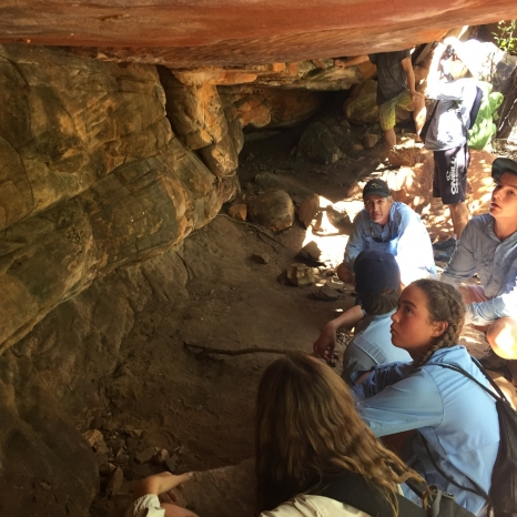 people sitting in cave looking at aboriginal art