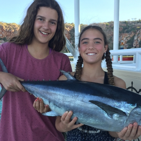 young girls holding tuna