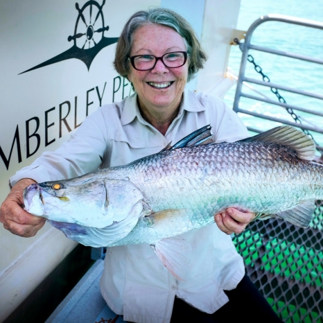 woman holding caught barramundi